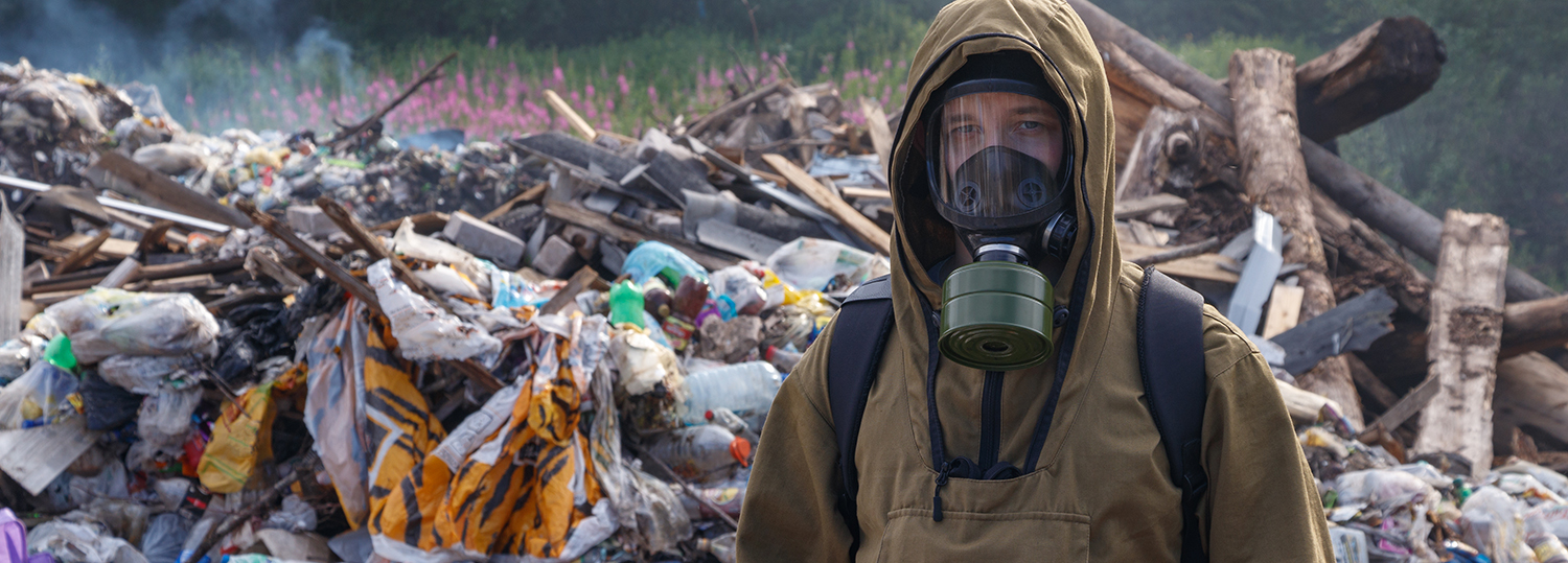 A working man in a gas mask against the backdrop of burning garbage.