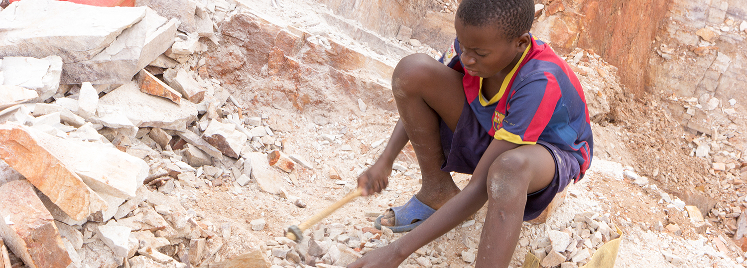 Ugandan child breaking rocks into small slabs for sale to his foreman.